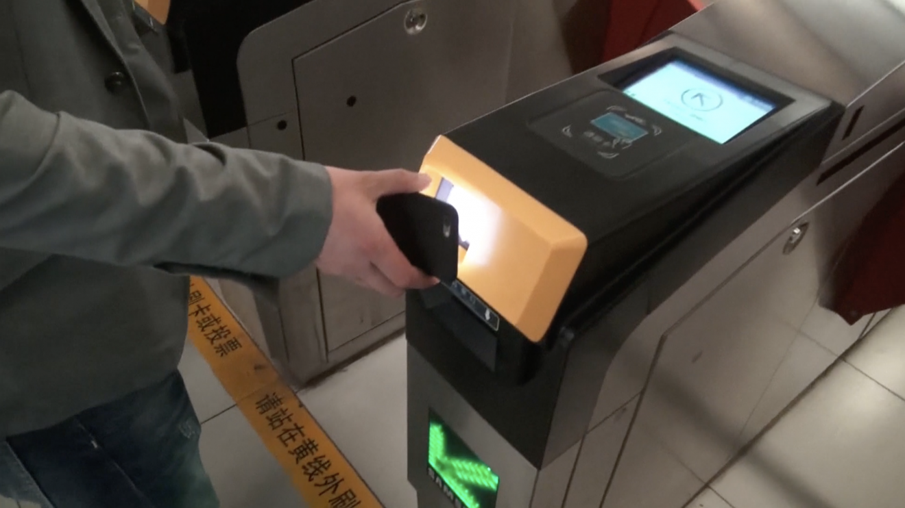A passenger getting through subway gate by scanning a QR code