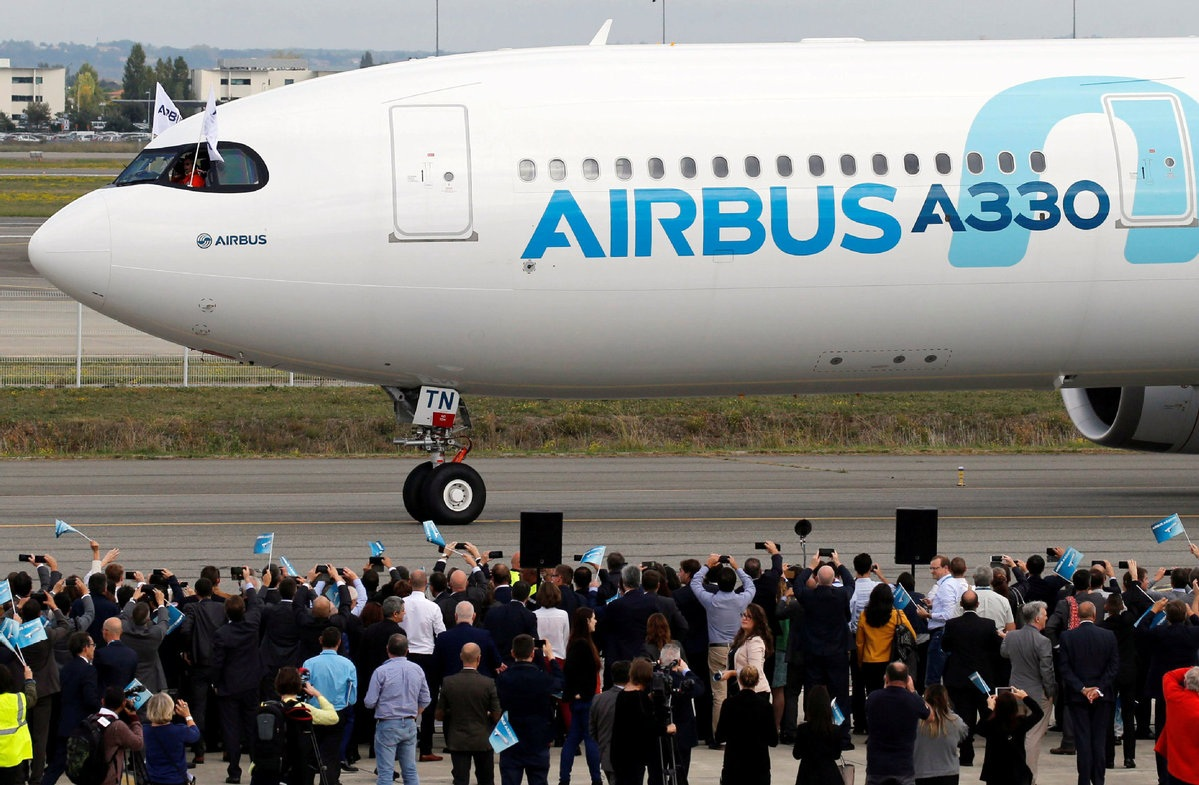 People celebrate near an Airbus A330neo aircraft after its maiden flight event in Colomiers near Toulouse France
